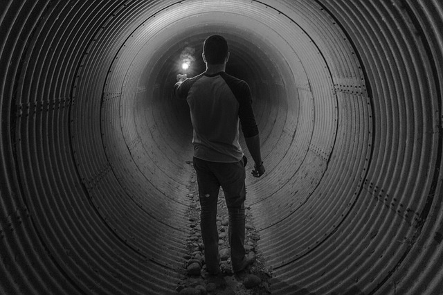 Person inside a sewer pipe lighting the way ahead with a torch