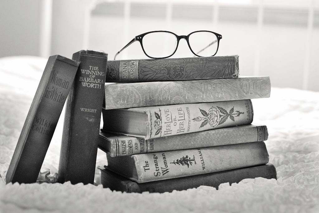 Black and white photo of a stack of books, with a pair of glasses rested on top